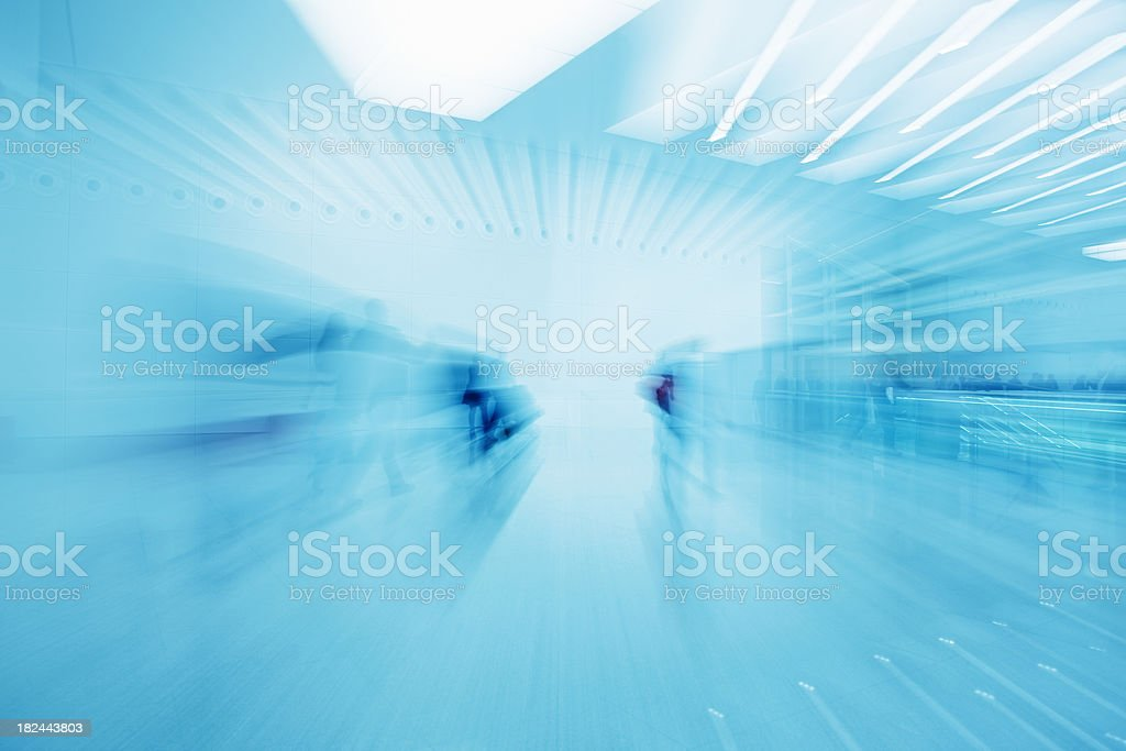 People Walking in Modern Interior, Zoom Blur, Blue Toned Image royalty-free stock photo