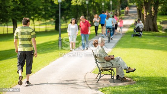 People walking on footpath in park, senior couple sitting on park bench.