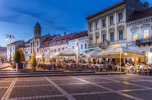 Menschen, die auf dem Ratsplatz (Piaa Sfatului), Brasov, Rumänien spazieren gehen – Foto