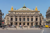 People walking in the Place de l´opera (Opera square) next to the Palais Garnier Opera House (Opera du Paris) at Paris city, France. Inaugurated in 1875, it is one of the most famous places in Paris.