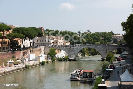 People walking in the Tiber riverside next to the Ponte Cestio (Pons Cestius) and the Tiber Island at Rome city, Italy.