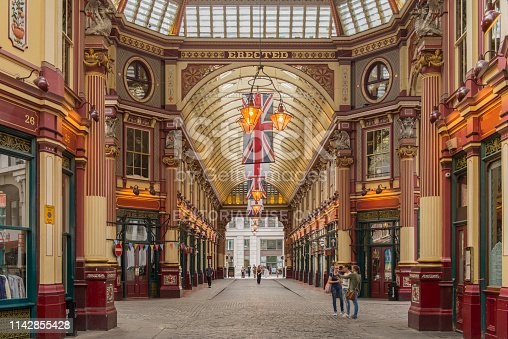 People walking inside of the Leadenhall Market at London, England, UK. This tourist attraction was built in the 14th century and it is located in the historic centre of the City of London.