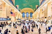 istock People walking moving in Grand Central Station aerial view in NYC main hall, floor, transportation concourse, american flag, windows, timetable 928013258
