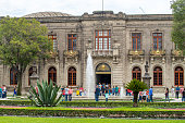 People walking next to a water fountain at the entrance of the Chapultepec Castle at Mexico city, Mexico.