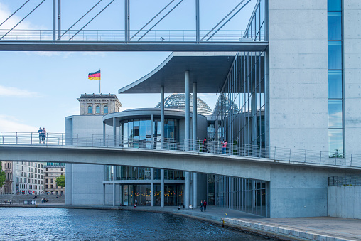 People walking next to the Marie-Elisabeth-Lüders-Haus building, part of the Bundestag and the Spree River at Berlin, Germany.