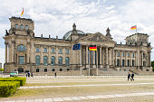 People walking next to the Reichstag Building at central Berlin city, Germany.