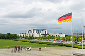 People walking next to the Reichstag Building at Berlin city, Germany. This government building is part of the Bundestag buildings. At the background the modern German Chancellery building.