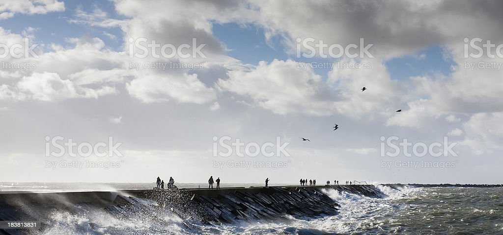 People walking on a dyke with storm in IJmuiden, Holland stock photo