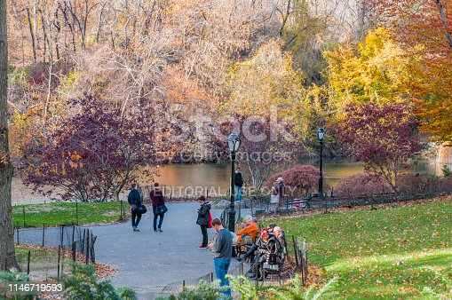 People walking on a footpath and sitting on benches next to a pond during a sunny autumn day in Central Park, midtown Manhattan, New York City. USA.