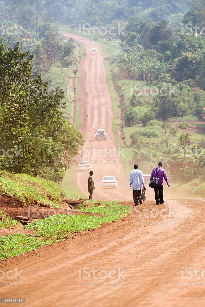 People walking on an african dusty dirt road. stock photo