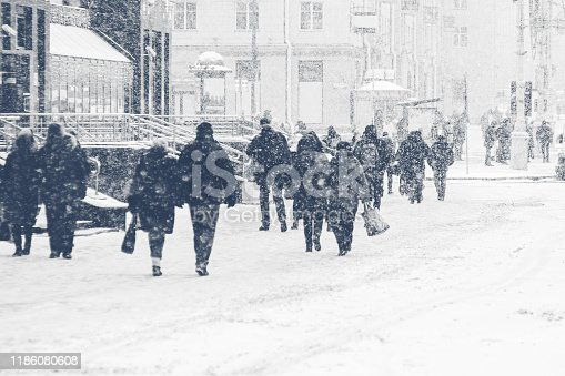 Winter city sidewalk. Rear view of people walking along an icy snowy pavement. City dwellers in the winter. Abstract winter weather background