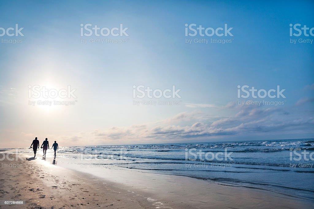 People walking on beach at sunrise - foto de stock