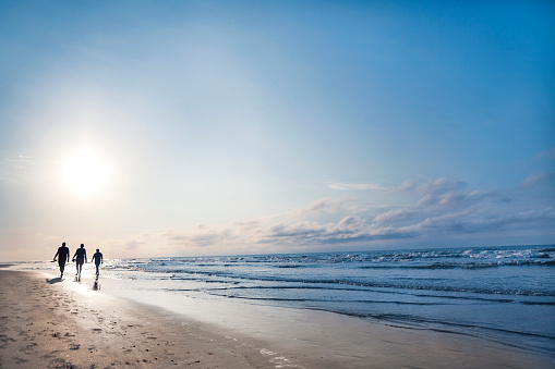 People walking on beach at sunrise