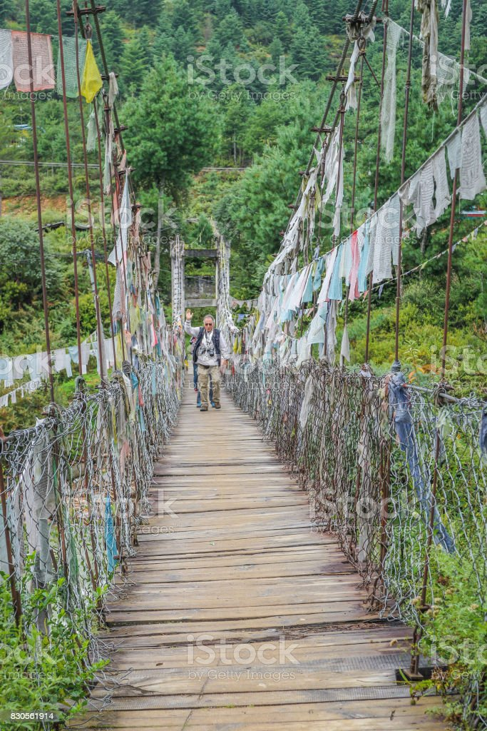 People walking on Bhutanese pedestrian suspension bridge with prayer flags in greenery area, Bhutan. stock photo