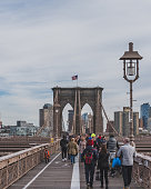 New York City, USA - Oct. 19, 2018: People walking on Brooklyn Bridge with buildings of Brooklyn in background