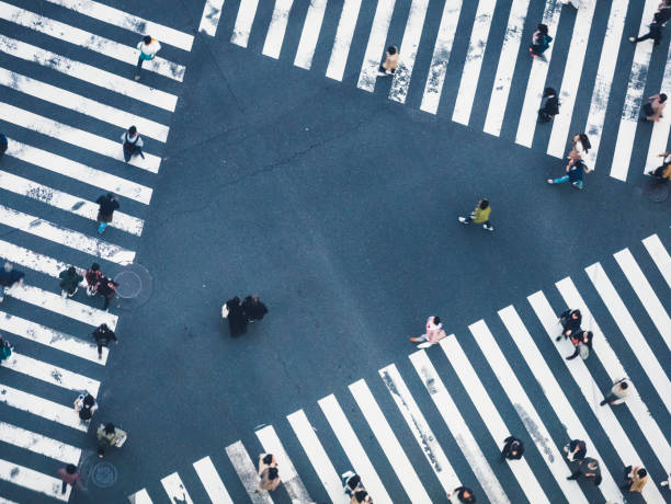 People walking on Crossing city street crosswalk top view stock photo