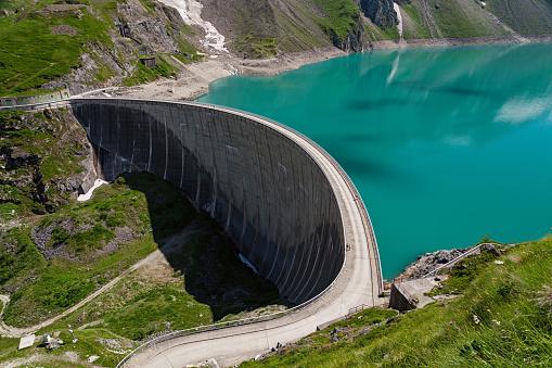Tourists walking on big concrete Dam, Kaprun, Austria