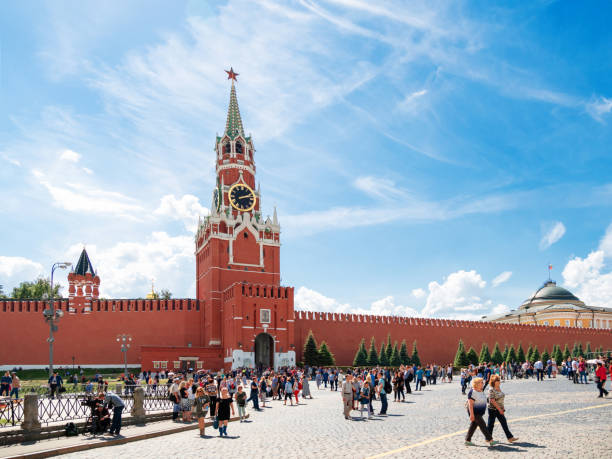 People walking on Red square near Spasskaya tower. Famous landmark with crowds of locals and tourists. stock photo