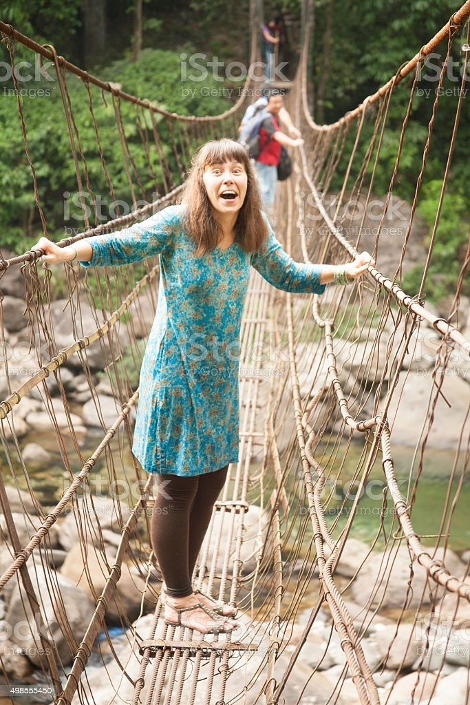 People walking on rustic cable, wire suspension bridge. stock photo