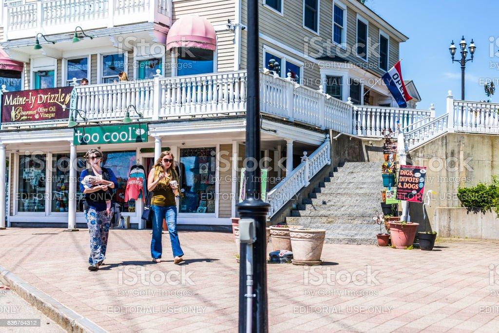 People walking on sidewalk street in downtown village during summer day stock photo