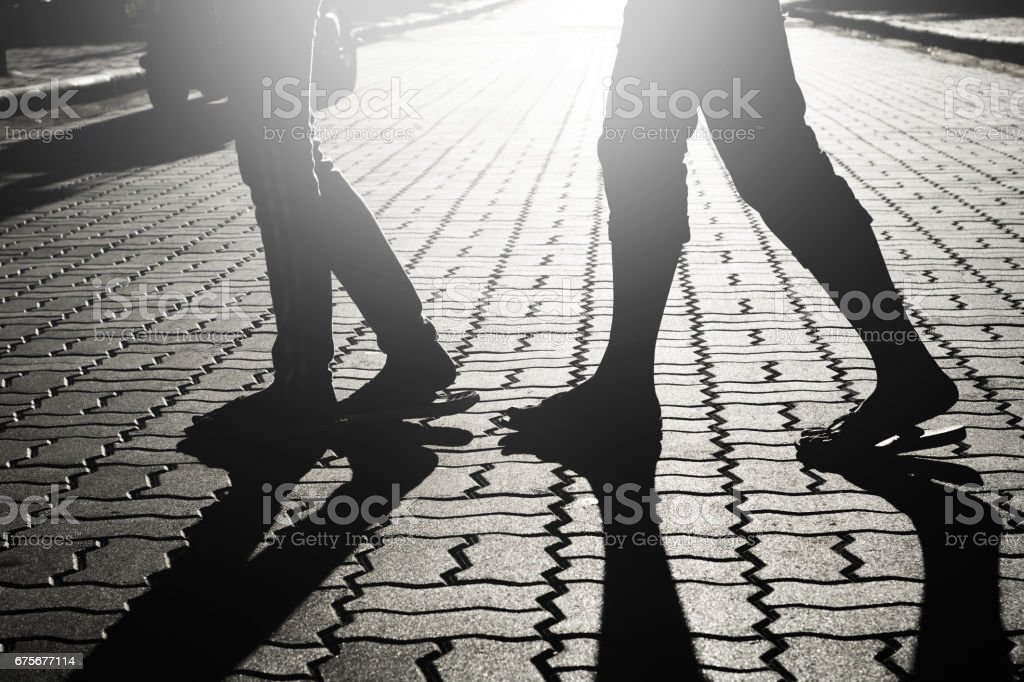 People walking on street sidewalk with shadow silhouette royalty-free stock photo