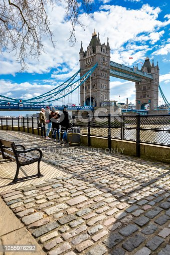London, England - Aug 22, 2019: People walking on the Thames Promenade with London Tower Bridge in background. Many people are looking at the bridge or are taking pictures.