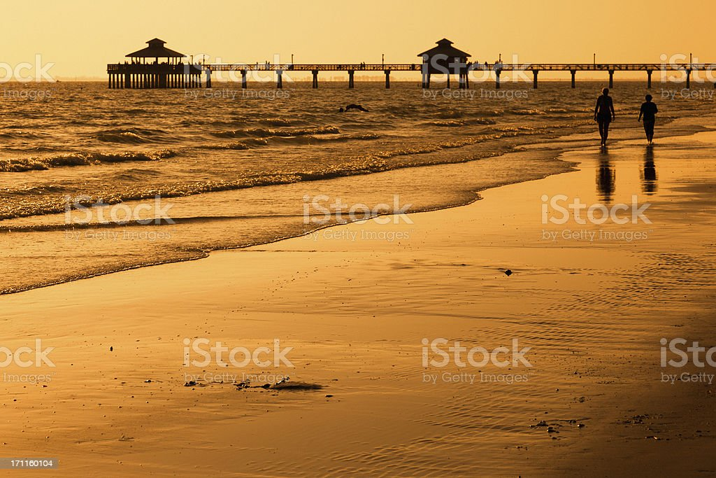 People walking on the Beach at Sunset stock photo