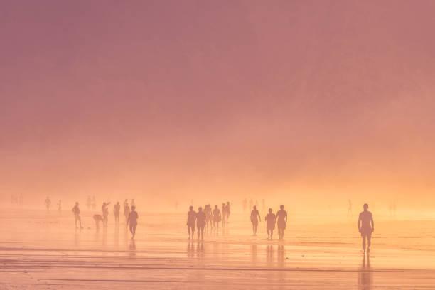 gente caminando en la playa - foto de stock