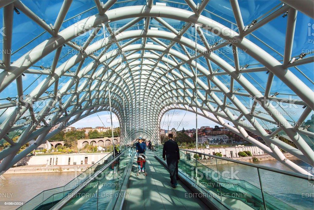 People walking on the Bridge of Peace, contemporary design landmark of Tbilisi stock photo