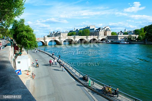 Paris, France - April 22, 2018: People walking on the quay along the Seine River in Paris
