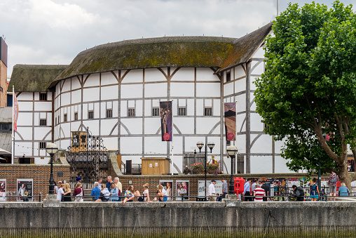 People walking on the Thames River coast sideway next to the Shakespeare Theatre, know as