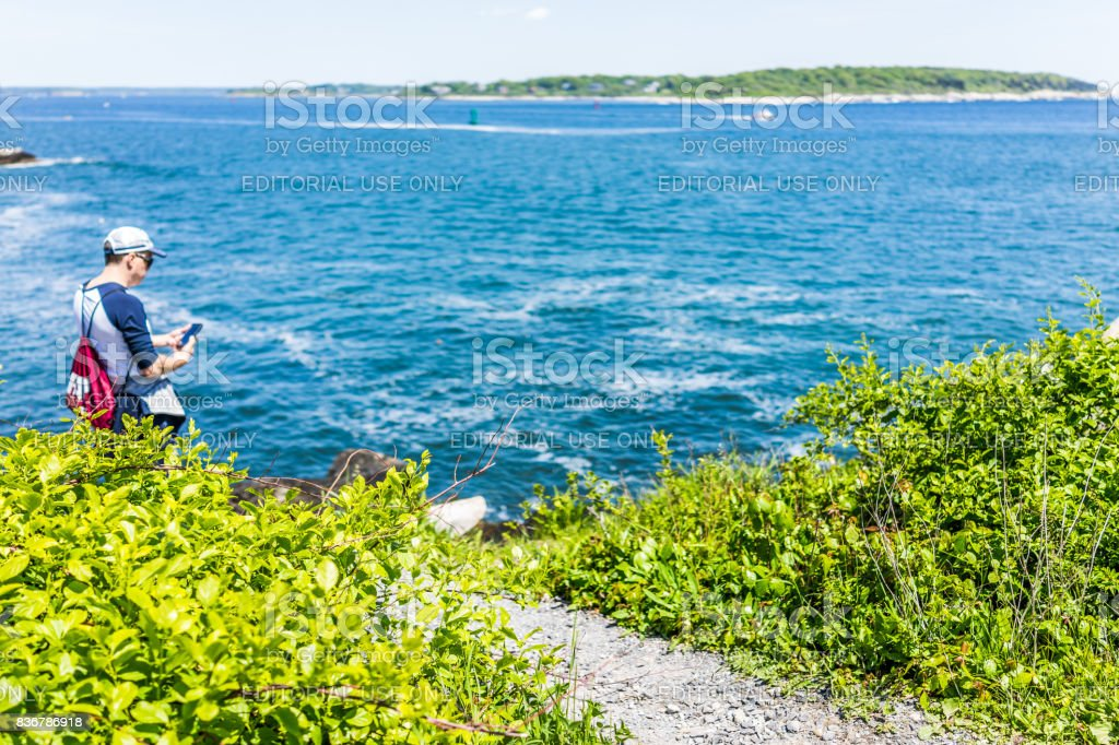 People walking on trails by Portland Head Lighthouse in Fort Williams park in Maine during summer overlooking Cushing Island stock photo