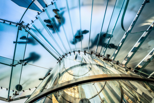 istock People walking on transparent glass staircase 180698194