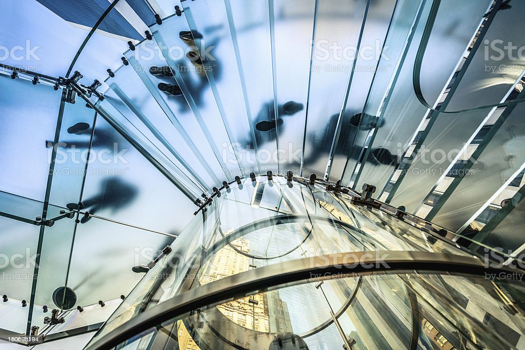 People walking on transparent glass staircase stock photo