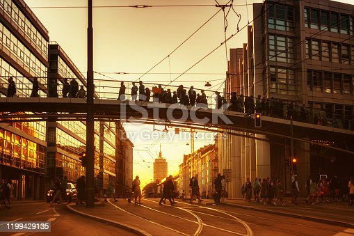 people walking over pedestrian bridge in munich at sunset hour home from oktoberfest