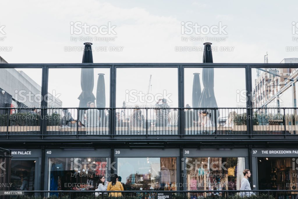 People walking past and sitting at the roof cafe at BOXPARK Shoreditch, London, UK stock photo