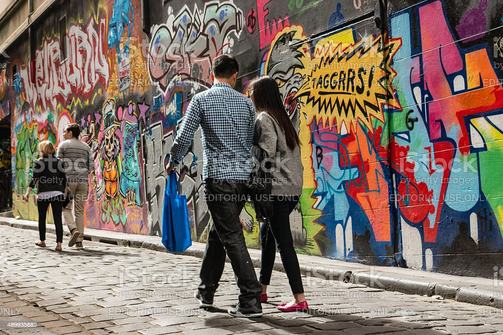 people walking past graffiti wall stock photo