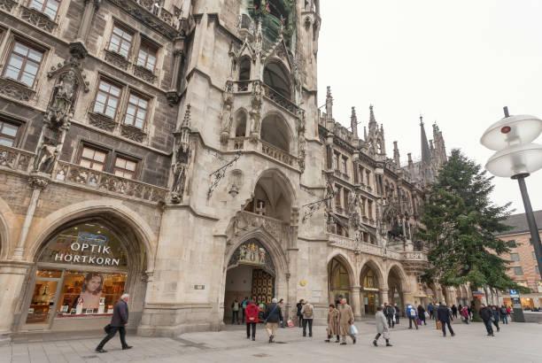 menschen zu fuß vorbei an historischen neo-gotischen stil neue rathaus in münchen - arbeit in münchen stock-fotos und bilder