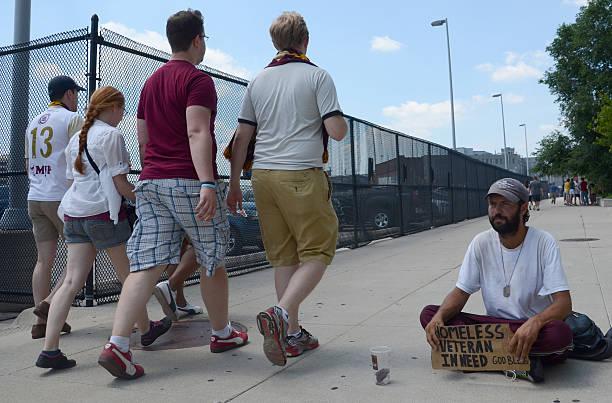 People walking past homeless veteran stock photo