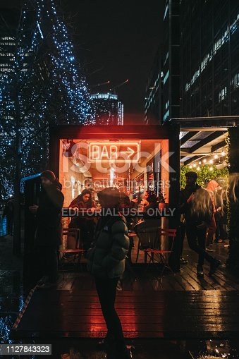 istock People walking past illuminated window and neon sign on Bar in Canary Wharf, London, UK. 1127843323