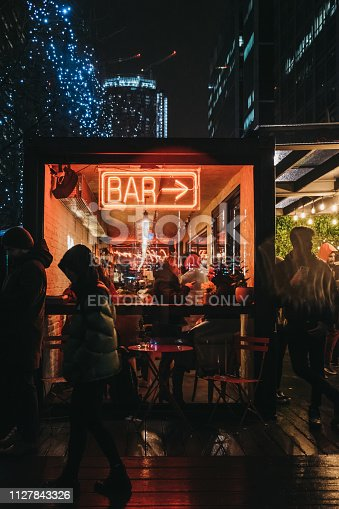 istock People walking past illuminated window and neon sign on Bar in Canary Wharf, London, UK. 1127843326