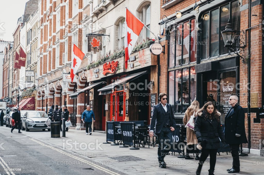 People walking past Maple Leaf Canadian bar on Maiden Lane in Covent Garden, London, UK. stock photo