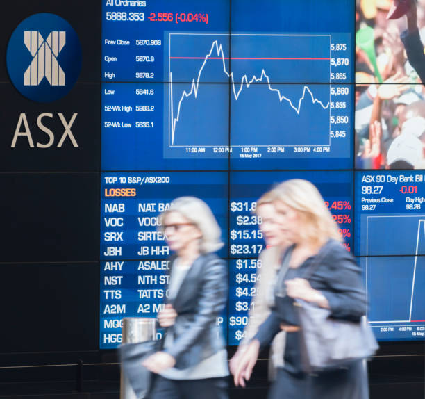 People walking past the electronic display board of the Sydney Exchange Square stock photo