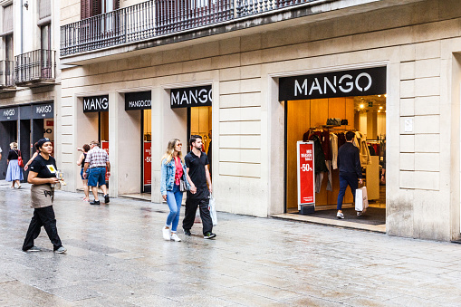 People walking past the Mango clothing store.