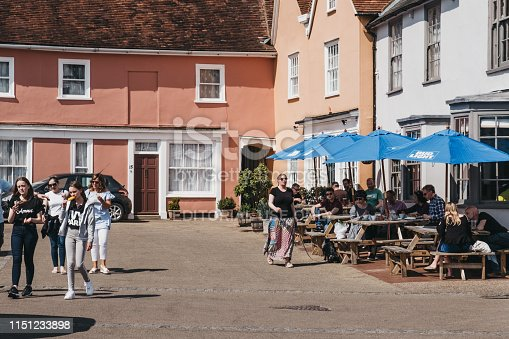 Lavenham, UK - April 19, 2019: People walking past the outdoor pub tables in Lavenham, a village in Suffolk, England, famous for its Guildhall, Little Hall and its architecture.