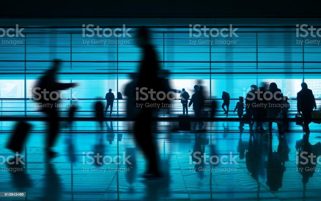 People walking reflection in airport corridor stock photo