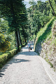 Lenno, Italy - July 8, 2017: People walking the Greenway trail near Lenno, Italy. Greenway Lake Como is a landscape trail of 11.2 km in the nature on the west shore of the lake.