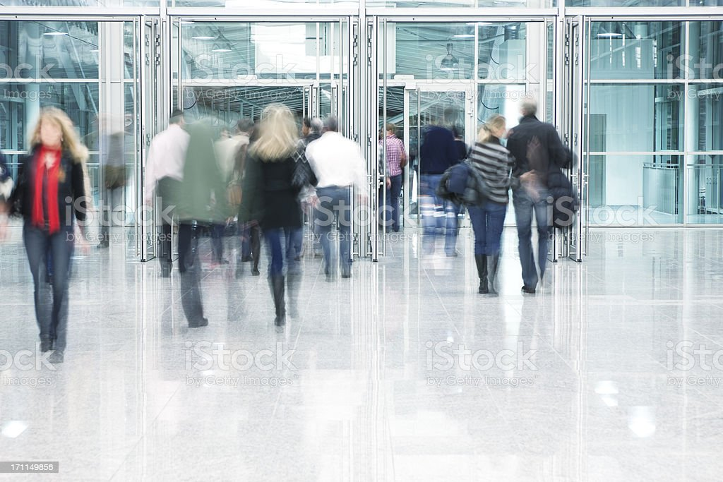 People Walking Through Entrance Door in Modern Building, Blurred Motion royalty-free stock photo