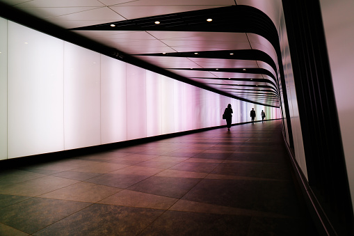 istock People walking through futuristic looking pedestrian tunnel featuring an LED integrated light wall in Granary Square exit from Kings Cross Underground station. 866605998