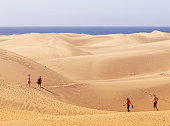 Maspalomas, Spain - June 18, 2012: small group of people walking through the Sand Dune of Maspalomas to the beach (Gran Canaria).